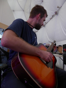 Chief Engineer Andrzej Stewart plays his guitar in the common area.