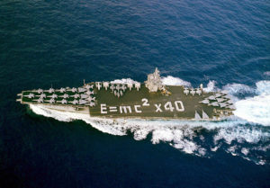 "Sailors aboard USS Enterprise spell out ""E = MC2x40"" on the carrier's flight deck to mark forty years of U.S. Naval nuclear power as ship and crew return home from a deployment in support of Operation Enduring Freedom. U.S. Navy Photo by Photographer's Mate 3rd Class Douglass M. Pearlman. (RELEASED). Courtesy of Wikimedia Commons."